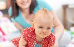 Портрет усмехаясь ребенка с ее матерью на предпосылке стоковое фото