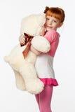 Портрет усмехаясь рыжеволосой девушки в розовой рубашке обнимая th Стоковые Фотографии RF