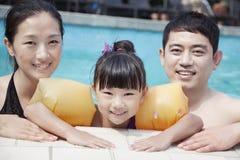 Портрет усмехаясь семьи в бассейне краем смотря камеру Стоковые Фотографии RF