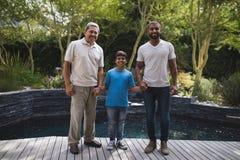 Портрет усмехаясь семьи мульти-поколения держа руки на крылечке Стоковая Фотография