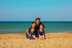 Портрет усмехаясь семьи на пляже против моря Стоковое Фото