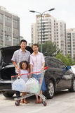 Портрет усмехаясь семьи при магазинная тележкаа стоя рядом с автомобилем, outdoors Стоковое Фото