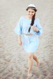 Портрет усмехаясь смеясь над белой кавказской женщины брюнет с загоренной кожей в голубом платье и соломенной шляпе бежать на пля Стоковая Фотография