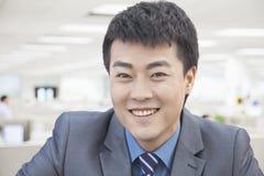 Портрет усмехаясь среднего взрослого бизнесмена, смотря камеру Стоковое Фото