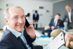 Портрет усмехаясь старшего бизнесмена говоря на Smartphone внутри Стоковые Изображения