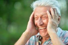 Портрет усмехаясь старшего человека в парке стоковое фото