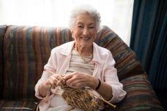 Портрет усмехаясь старшей женщины вязать пока сидящ на софе против окна Стоковое Изображение