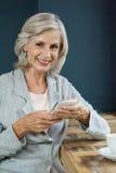 Портрет усмехаясь старшей женщины держа мобильный телефон пока сидящ на таблице Стоковая Фотография