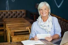 Портрет усмехаясь старшей женщины держа цифровую таблетку пока сидящ на таблице Стоковое Изображение
