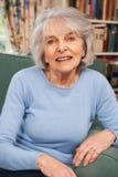 Портрет усмехаясь старшей женщины сидя в кресле стоковые изображения rf