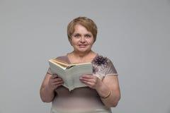 Портрет усмехаясь старшей женщины с книгой Стоковое Изображение RF