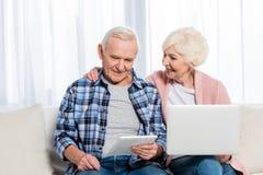 портрет усмехаясь старших жены и супруга используя цифровые приборы стоковая фотография rf