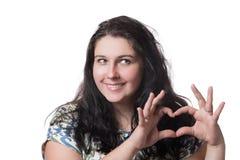 Портрет усмехаясь счастливой молодой женщины делая знак сердца при изолированные руки на белой предпосылке Положительные человече Стоковое фото RF