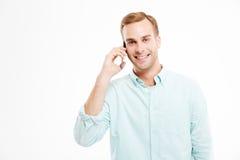 Портрет усмехаясь уверенно молодого бизнесмена говоря на мобильном телефоне Стоковое Изображение RF