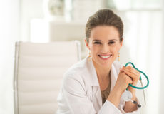 Портрет усмехаясь усаживания женщины врача стоковое фото rf