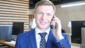 Портрет усмехаясь успешного предпринимателя бизнесмена работая на офисе Стоковое Изображение