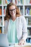 Портрет усмехаясь учителя используя компьтер-книжку в библиотеке стоковое изображение rf