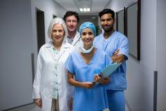 Портрет усмехаясь хирургов и доктора стоя в коридоре Стоковое фото RF