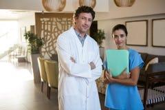 Портрет усмехаясь хирургов и доктора стоя при пересеченная рука Стоковое Изображение