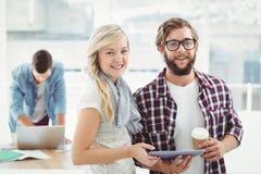 Портрет усмехаясь человека и женщины работая на цифровой таблетке Стоковые Фото