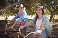 Портрет усмехаясь человека и женщины сидя на велосипедах Стоковые Изображения RF