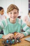 Портрет усмехаясь школьника работая на электронном проекте Стоковое Изображение