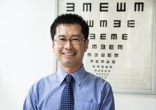Портрет усмехаясь optometrist с диаграммой глаза на заднем плане Стоковые Изображения