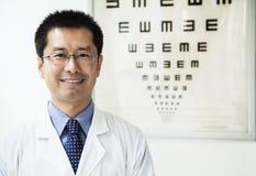 Портрет усмехаясь optometrist с диаграммой глаза на заднем плане Стоковая Фотография RF