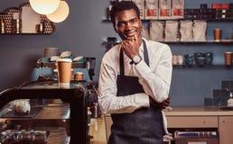 Портрет успешного Афро-американского мелкого бизнеса предпринимателя усмехаясь на камере пока стоящ на кофейне стоковое фото