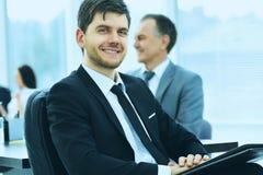 Портрет успешного бизнесмена в офисе на предпосылке их команды Стоковое фото RF