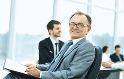 Портрет успешного бизнесмена в офисе на предпосылке работы команды Стоковая Фотография