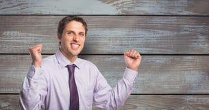 Портрет успешного бизнесмена обхватывая зубы и кулаки против деревянной стены Стоковая Фотография