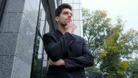 Портрет успешного задумчивого бизнесмена в городе Человек в куртке делового костюма на предпосылке офисного здания красиво сток-видео
