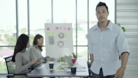 Портрет успешного красивого азиатского главного творческого бизнесмена усмехаясь к камере пока работающ в офисе акции видеоматериалы