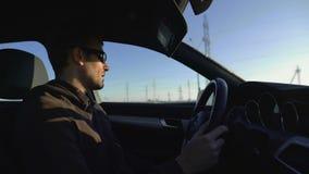 Портрет успешного мужского предпринимателя с солнечными очками, говорит на камере пока управляющ автомобилем сток-видео