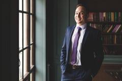 Портрет успешного положения бизнесмена в дорогом деловом костюме около окна в его офисе и усмехаться стоковые фото