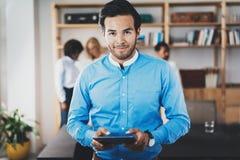 Портрет успешного уверенно испанского бизнесмена держа таблетку в руках и смотря камеру в современном офисе Стоковые Фото