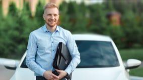 Портрет успешного усмехаясь молодого портфеля удерживания бизнесмена представляя на белой предпосылке автомобиля акции видеоматериалы