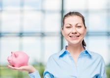 Портрет успешной женщины с розовой копилкой Стоковое фото RF