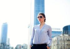Портрет успешной коммерсантки в голубых рубашке и солнечных очках в большом городе Стоковая Фотография