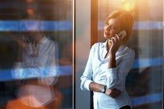 Портрет успешной коммерсантки говоря на ее мобильном телефоне пока стоящ около большого окна в современном интерьере офиса Стоковое Изображение