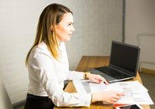 Портрет успешной коммерсантки работая с компьтер-книжкой в офисе Стоковые Изображения RF
