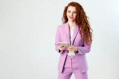 Портрет успешной счастливой красивой бизнес-леди с краснокоричневыми волосами и состава в розовом костюме держа таблетку, смотря  Стоковые Изображения