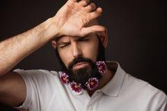 Портрет утомленного небритого человека с бородой и усика с хризантемой цветет Стоковые Фото