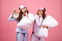 Портрет 2 утомлял милые девушек одетые в пижамах зевая Стоковое Фото