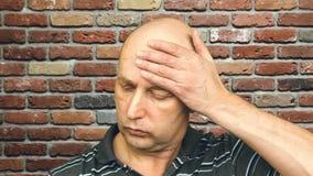 Портрет утомлял человека обтирая лоб и смотря камеру на предпосылке кирпича видеоматериал