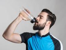 Портрет утомленной питьевой воды велосипедиста от контейнера бутылки Стоковое Изображение