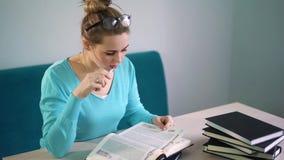 Портрет ухищренного студента с открытой книгой читая его в библиотеке колледжа видеоматериал