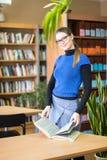 Портрет ухищренного студента в библиотеке Стоковая Фотография