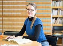 Портрет ухищренного студента в библиотеке Стоковая Фотография RF